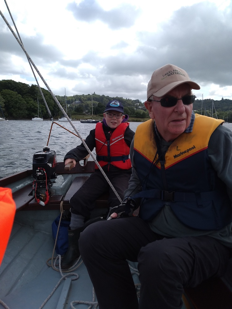 Man and boy on sailing boat at windermere - Cumbria Deaf Association